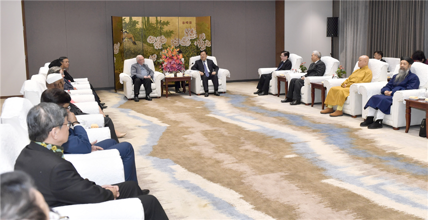 Xia Baolong meets with overseas delegates to cross-religious symposium