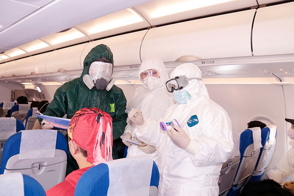 A police officer and medical workers check the body temperature of passengers onboard a flight at Putuoshan Airport in Zhoushan, Zhejiang province, Jan 28, 2020.jpg