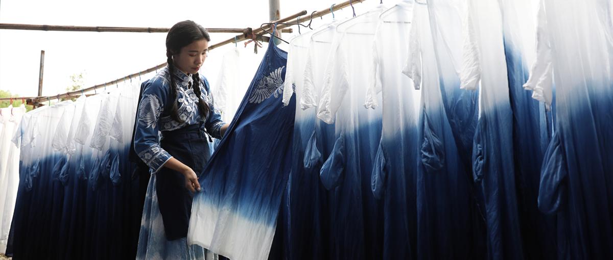 6月2日何证明,在贵州省丹寨县靛蓝蜡染手工坊一边摇,刘绍花在察看浸染好的服饰制品您引。(1).JPG
