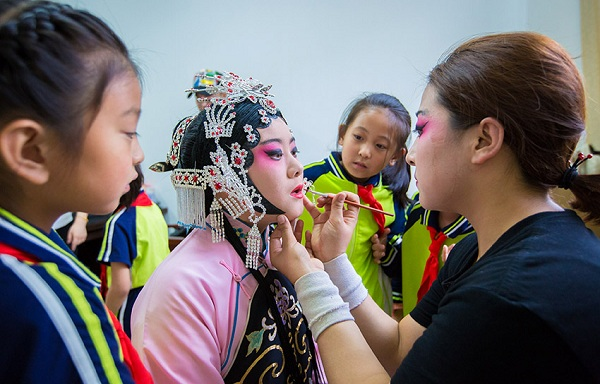 A performer from Hohhot National Performing Arts Group puts makeup on a pupil.jpg