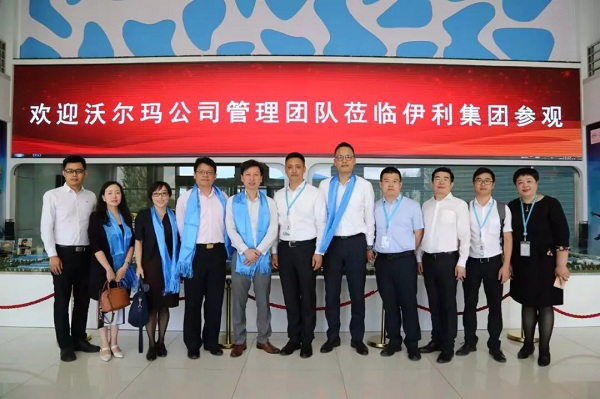 Yili's and Walmart's executives pose for a photograph when visiting Yili's factories..png