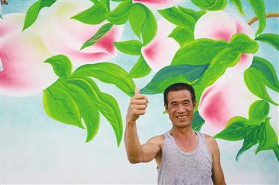 A smiling villager pictured with peaches painted on the shed wall at Yematu village, Hohhot, Inner Mongolia.png