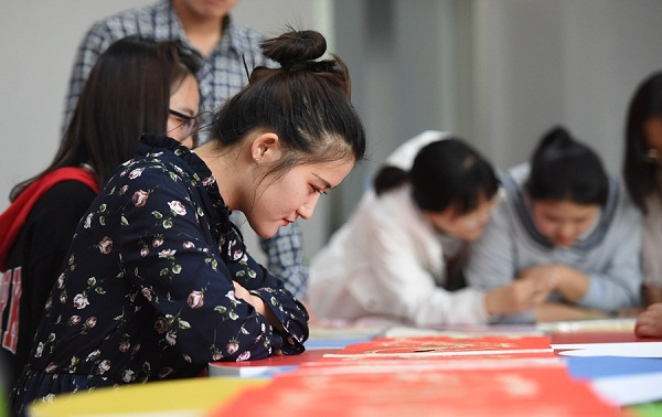 An IMNU student views wheat straw paintings in the class.jpg