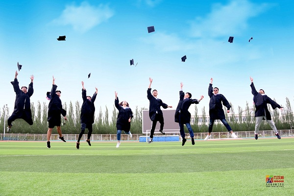 Graduates at IMNU throw their graduation caps into the air.jpg