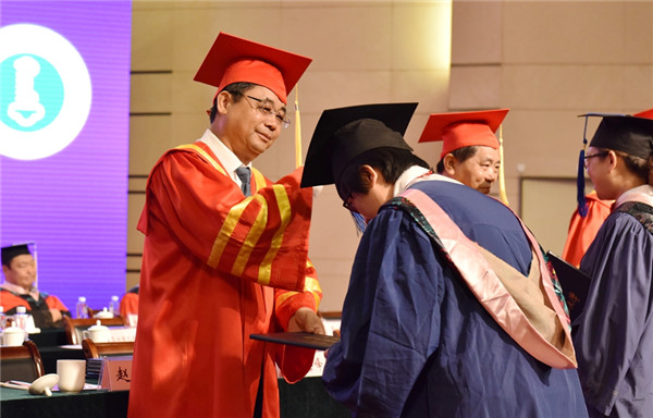 Graduates receive diplomas from the president and vice-president of IMNU during the ceremony, July 3..jpg