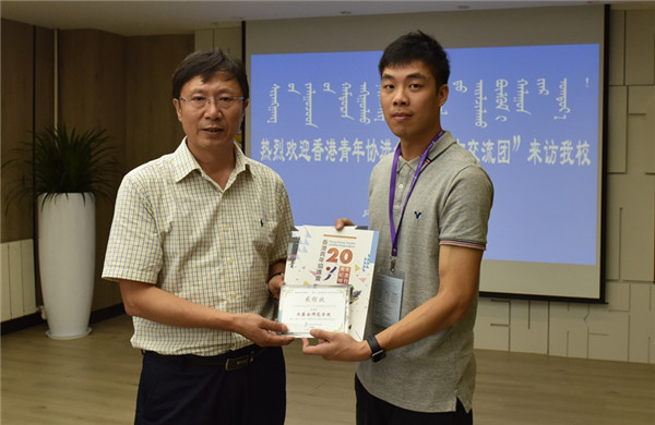 Xie Chunyuan, director at the Hongkong Youth Unified Association (L) gives a Certificate of Appreciation to IMNU, August 7.jpg