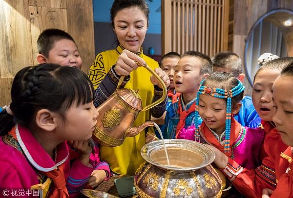 2018年9月14日,呼和浩特市玉泉区民族实验小学的学生在学习熬制奶茶。.jpg