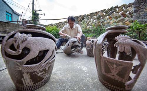 Villager carves animals on vats
