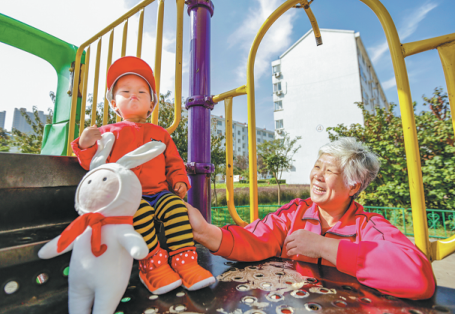 A child and an elderly resident enjoy playground facilities provided in the Weifang Hi-Tech Industrial Development Zone.png