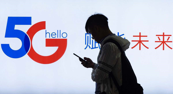 A pedestrian walks past a 5G promotion board. [Photo by Su YangFor China Daily].jpg