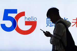 A pedestrian walks past a 5G promotion board. [Photo by Su YangFor China Daily]_副本.jpg